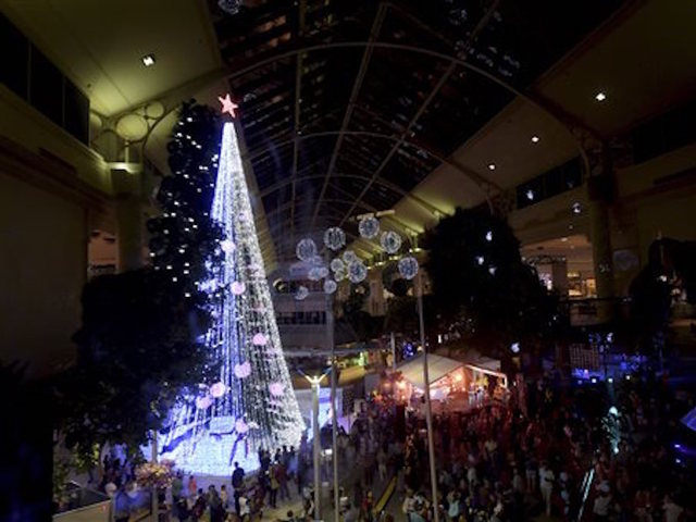 27, 2015 photo, people gather to observe a Guinness World Records attempt for the most lights on an artificial Christmas tree in Canberra, Australia.